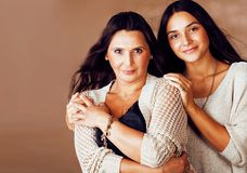Cute pretty teen daughter with mature mother hugging, fashion st. Yle brunette makeup close up tann mulattos, warm colors close up royalty free stock photography