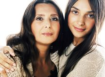 Cute pretty teen daughter with real mature mother hugging, fashi. On style brunette makeup close up tann mulattos, warm colors isolated on white background stock photography