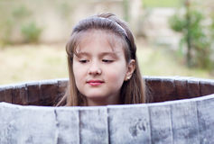 Cute pretty young girl hiding in a barrel Royalty Free Stock Image