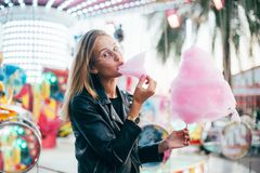 Young pretty woman blogger with cotton candy. Cute and pretty young girl or student, eats and poses with sugar pink candy cotton, wears leather jacket in line Stock Image