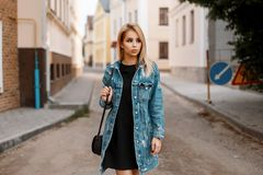 Cute pretty young woman in a black stylish dress with a fashionable handbag in a trendy long denim jacket posing in a city. On the street near vintage buildings royalty free stock photo