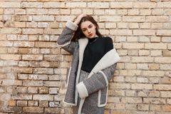 Cute pretty young woman in elegant checkered coat with white fur in a black stylish t-shirt in vintage gray pants. Posing near a brick wall. Fashionable royalty free stock photography