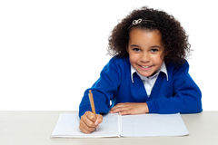 Cute primary kid writing her assignment Stock Photos