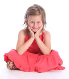 Cute primary school girl sitting cross legged. Cute blonde six year old primary school girl wearing coral pink dress sitting cross legged on floor with a happy Royalty Free Stock Photo
