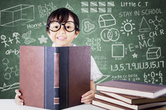 Cute primary school student reading books in class Royalty Free Stock Photo
