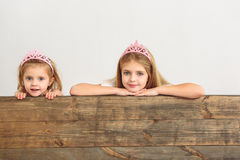 Cute princesses peeping over wooden border royalty free stock image