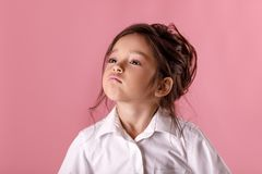 Cute proud little girl in white shirt on pink background. Human emotions and facial expression royalty free stock photo