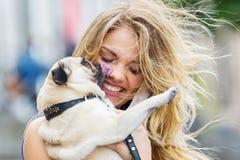 Pug licks the face of a pretty woman. Cute pug licks the face of a pretty woman Royalty Free Stock Photos