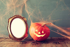 Cute pumpkin next to blank photo frame Royalty Free Stock Image