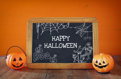 Cute pumpkins next to blackboard on wooden table Stock Photo