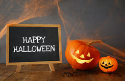 Cute pumpkins next to blackboard on wooden table Stock Image