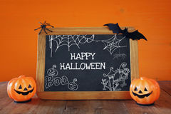 Cute pumpkins next to blackboard on wooden table Royalty Free Stock Photos