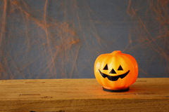 Cute pumpkins and spiders on wooden table Stock Photos