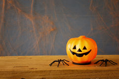 Cute pumpkins and spiders on wooden table Royalty Free Stock Photo