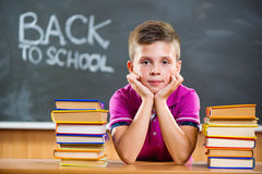 Cute pupil with books in classroom Stock Photo