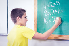 Cute pupil calculating on chalkboard in a classroom Stock Photo