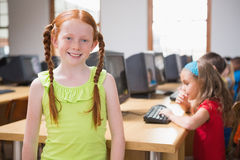 Cute pupil in computer class smiling at camera Royalty Free Stock Photography