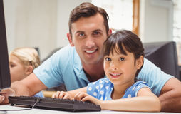 Cute pupil in computer class with teacher Royalty Free Stock Image