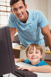 Cute pupil in computer class with teacher Stock Image