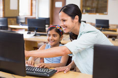 Cute pupil in computer class with teacher Stock Photo