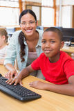 Cute pupil in computer class with teacher. At the elementary school Royalty Free Stock Image
