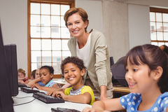 Cute pupil in computer class with teacher smiling at camera Stock Photo