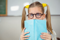 Cute pupil covering face with a book in a classroom Royalty Free Stock Photos