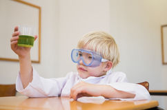 Cute pupil dressed up as scientist in classroom. At the elementary school stock photography