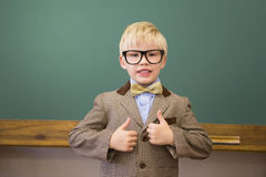 Cute pupil dressed up as teacher in classroom Stock Photos