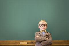 Cute pupil dressed up as teacher in classroom Stock Photography