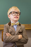 Cute pupil dressed up as teacher in classroom Stock Image