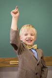 Cute pupil dressed up as teacher in classroom Stock Photo