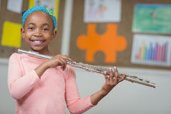 Cute pupil with flute in a classroom Stock Image