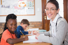 Cute pupil getting help from teacher in classroom Royalty Free Stock Photography
