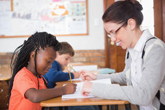 Cute pupil getting help from teacher in classroom Stock Photo