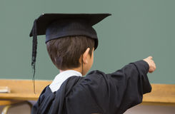 Cute pupil in graduation robe pointing in classroom Stock Image