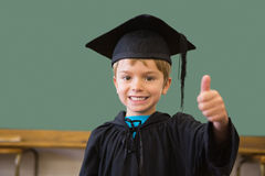 Cute pupil in graduation robe smiling at camera in classroom Stock Images