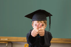 Cute pupil in graduation robe smiling at camera in classroom Royalty Free Stock Photo