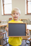 Cute pupil holding chalkboard in classroom Royalty Free Stock Photography
