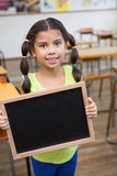 Cute pupil holding chalkboard in classroom Royalty Free Stock Photo