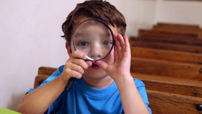 Cute pupil holding magnifying glass. In classroom at the elementary school stock video
