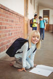 Cute pupil kneeling over notepad at corridor Stock Photo