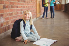 Cute pupil kneeling over notepad at corridor Stock Photography