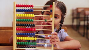 Cute pupil learning maths with an abacus. In classroom at the elementary school stock footage