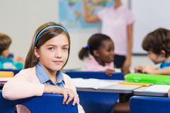 Cute pupil looking at camera during lesson Stock Photos