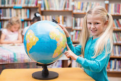 Cute pupil looking at globe in library Stock Photos