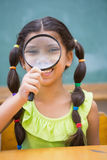 Cute pupil looking through magnifying glass in classroom Royalty Free Stock Image