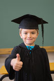 Cute pupil in mortar board smiling at camera in classroom Stock Photo