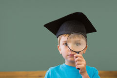 Cute pupil in mortar board smiling at camera in classroom. At the elementary school royalty free stock photography