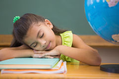 Cute pupil napping in classroom with globe Royalty Free Stock Image